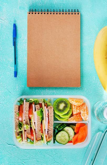 Schulbrotdose mit sandwich, gemüse, wasser und früchten auf tabelle. Kostenlose Fotos