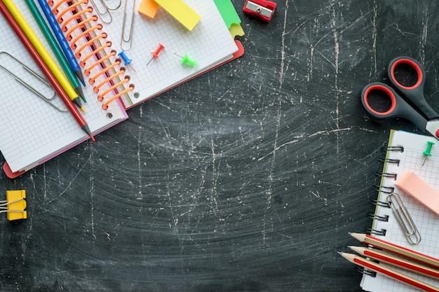 Schule und büroartikel auf einem tafelhintergrund. freier platz für text. ansicht von oben Premium Fotos