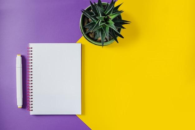 Schulheft auf gelbem und purpurrotem, gewundenem notizblock auf einer tabelle. draufsichthintergrund mit copyspace. büro notizblock flach zu legen. Premium Fotos