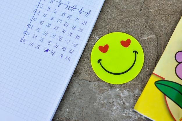 Schulhefte mit aufflackern emoticon auf fliesen im freien, vermehrungstabelle Premium Fotos