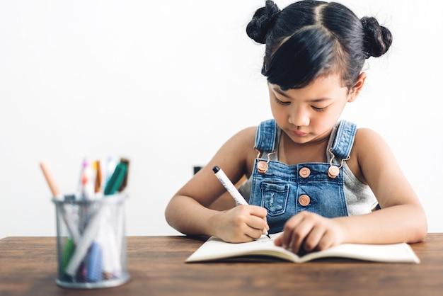 Schulkind kleines mädchen lernen und schreiben in