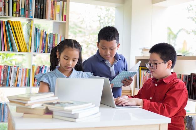 Schulkind macht seine hausaufgaben in der bibliothek in der schule. zurück zur schule. Premium Fotos