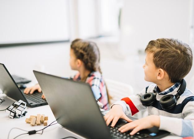 Schulkinder, die mit dem laptop betrachtet tafel sitzen Kostenlose Fotos