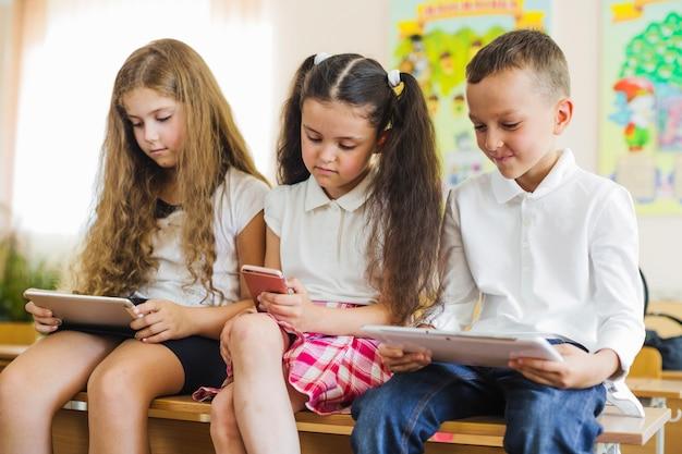 Schulkinder sitzen auf bank halten gadgets Kostenlose Fotos