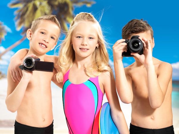 Schulkindkinder, die mit foto- und videokamera in händen stehen. Kostenlose Fotos