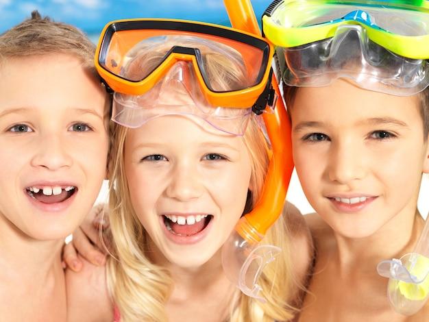 Schulkindkinder, die zusammen in der hellen farbbadebekleidung mit der schwimmmaske auf dem kopf stehen. Kostenlose Fotos