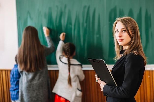 Schullehrer mit klemmbrett auf hintergrund der tafel und der studenten Kostenlose Fotos