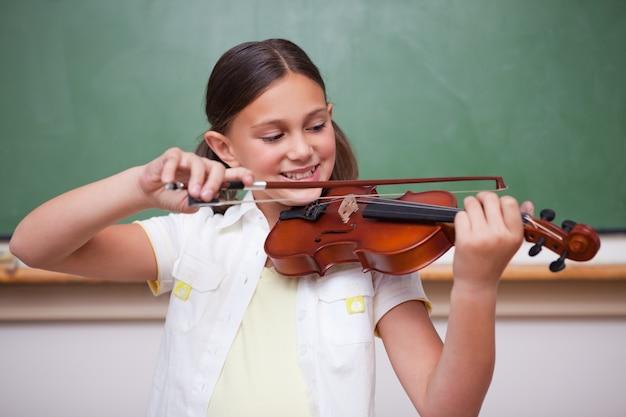 Schulmädchen, das die violine spielt Premium Fotos