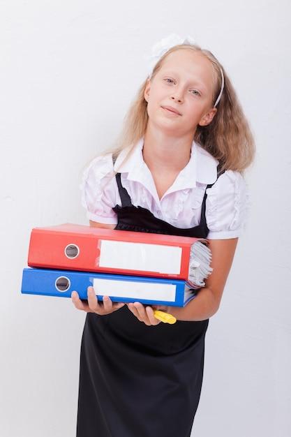 Schulmädchen, das stift und ordner in ihren händen über weißem hintergrund hält Kostenlose Fotos