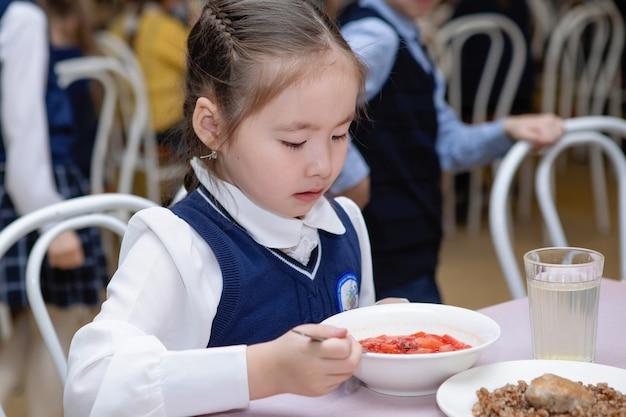 Schulmädchen in der kantine isst suppe Premium Fotos