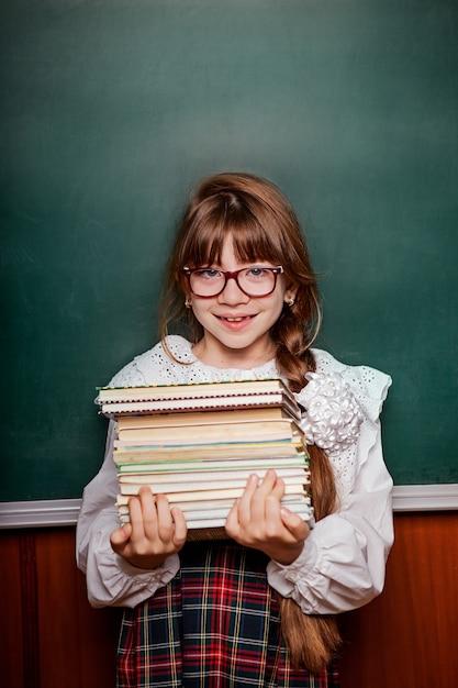 Schulmädchen in schuluniform mit einem stapel büchern, vor dem hintergrund einer schulbehörde Premium Fotos