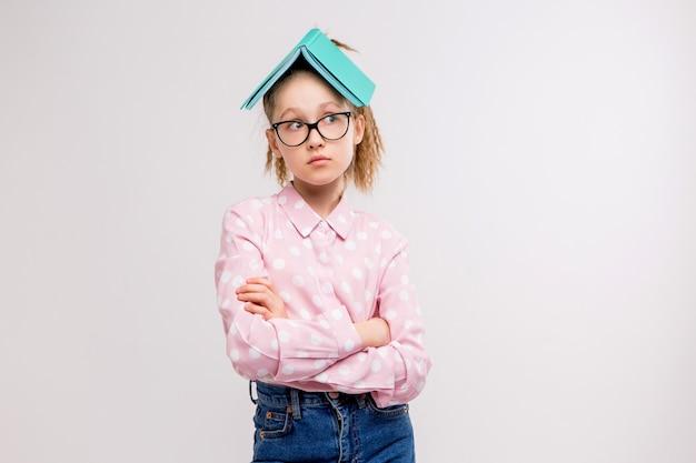 Schulmädchen mit brille mit einem buch auf dem kopf Premium Fotos