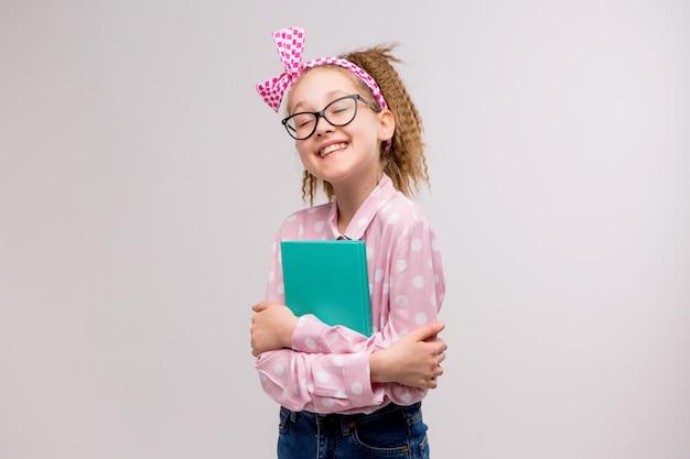 Schulmädchen mit brille mit einem buch lächelnd Premium Fotos