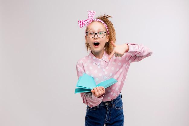 Schulmädchen mit brille mit einem buch Premium Fotos