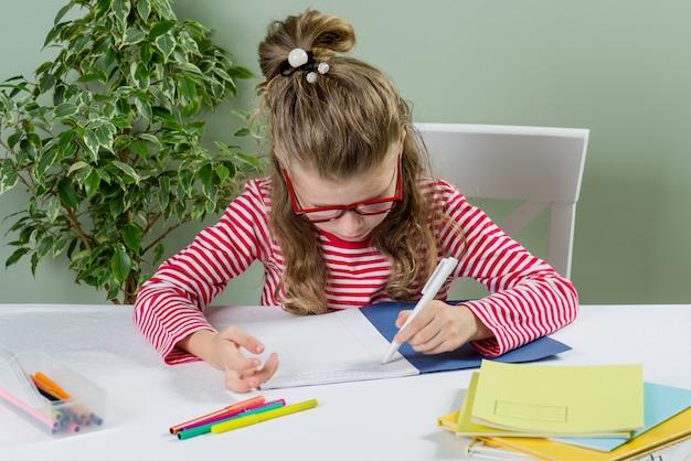 Schulmädchen mit brille schreibt etwas Premium Fotos