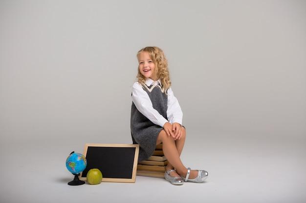 Schulmädchen mit büchern auf einem hellen hintergrund Premium Fotos
