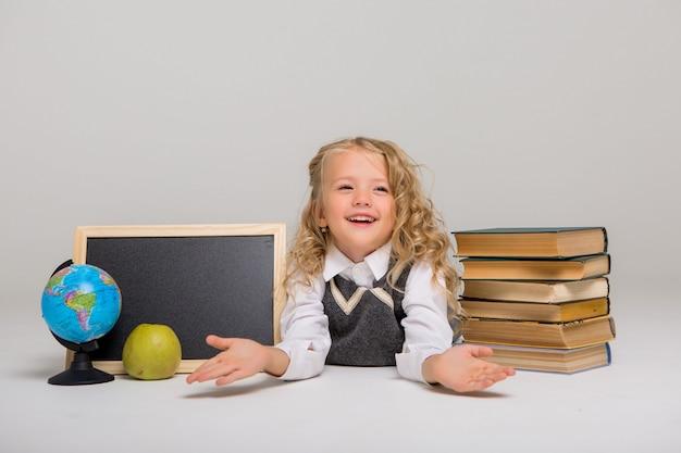 Schulmädchen mit büchern und leerem reißbrett auf weißem hintergrund Premium Fotos