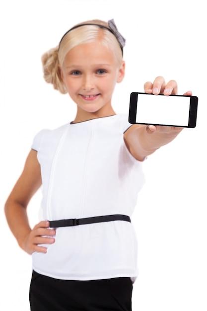 Schulmädchen mit dem handy in der hand, der die kamera betrachtet Premium Fotos