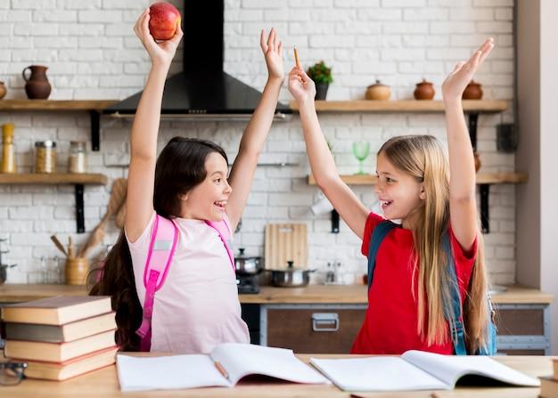 Schulmädchen mit den händen, die oben einander betrachten Kostenlose Fotos