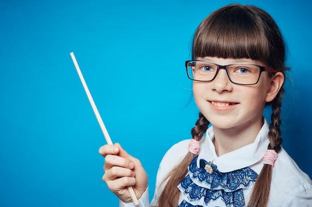 Schulmädchen mit gläsern und einem zeiger auf einem blauen hintergrund Premium Fotos