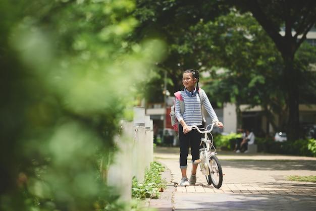 Schulmädchen mit rucksack nach der schule draußen gehend mit ihrem fahrrad Kostenlose Fotos