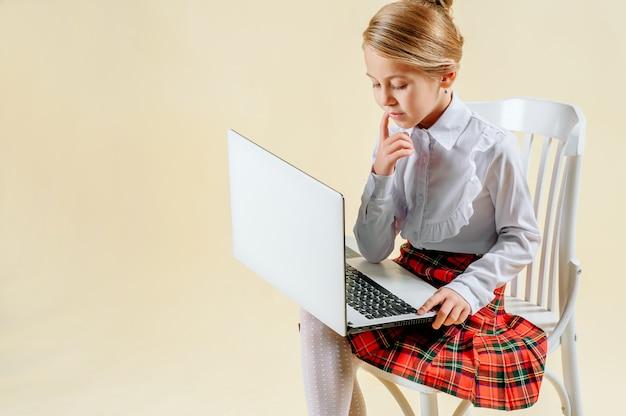 Schulmädchen schaut auf den laptop Premium Fotos