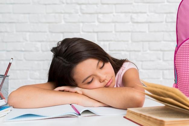 Schulmädchen schlafend mit kopf auf schreibheft Kostenlose Fotos
