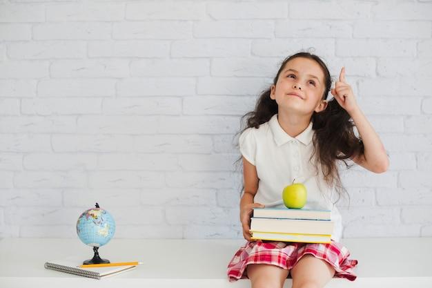 Schulmädchen sitzen und nach oben zeigen Kostenlose Fotos