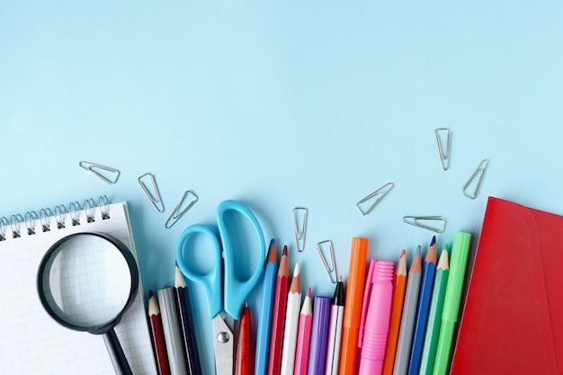 Schulmaterial auf blauem hintergrund. ansicht von oben. kopieren sie platz. Premium Fotos