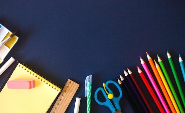 Schulmaterial auf dunkelblau Premium Fotos