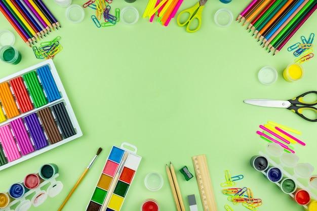 Schulmaterial auf einem grünen hintergrund Premium Fotos