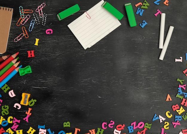 Schulmaterial: bunte holzstifte, notizbuch, papiersticker Premium Fotos