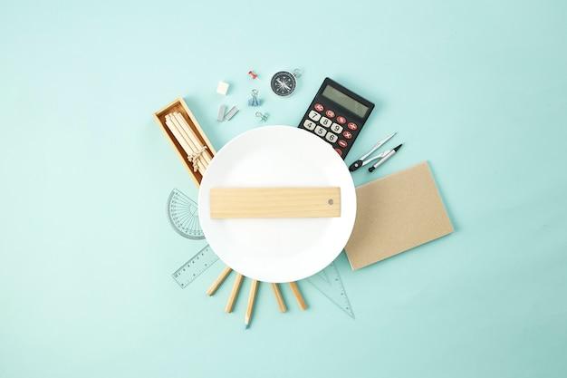 Schulmaterial rund um den leeren weißen teller Premium Fotos