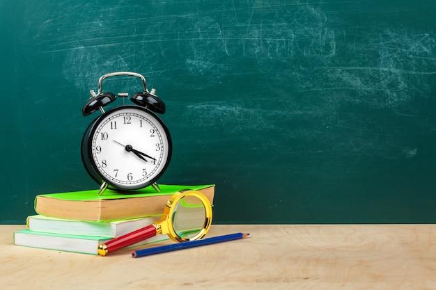 Schulmaterial. schreibgeräte und wecker. zeit, konzept zu studieren Premium Fotos