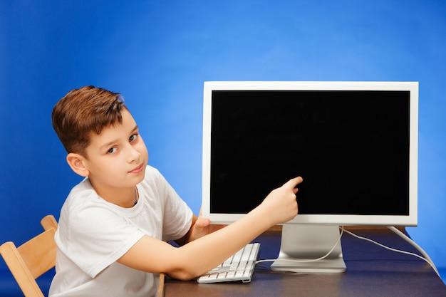 Schulpflichtiger junge, der mit dem monitorlaptop am studio sitzt Kostenlose Fotos