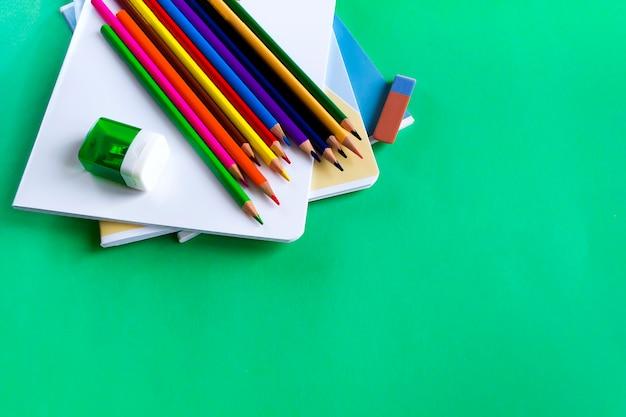 Schulsatz notizbücher, bleistifte, ein radiergummi und bleistiftspitzer auf grün Premium Fotos