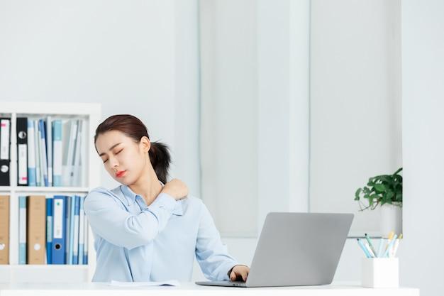 Schulterschmerzen der geschäftsfrau in einem büro Premium Fotos