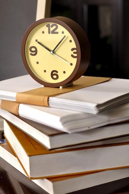 Schulzeit. wecker, der auf einen stapel bücher sitzt. konzept der bildung. Premium Fotos