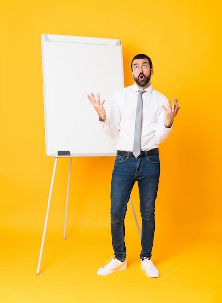 Schuss in voller länge des geschäftsmannes eine darstellung auf weißem brett über lokalisiertem gelb gebend frustriert durch eine schlechte situation Premium Fotos