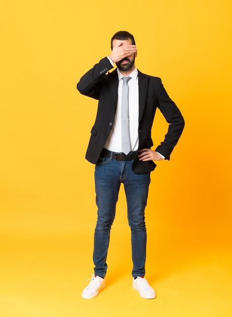 Schuss in voller länge des geschäftsmannes über lokalisierter gelber hintergrundbedeckung mustert durch hände, möchten nicht etwas sehen Premium Fotos
