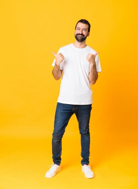 Schuss in voller länge des mannes mit bart über lokalisiertem gelbem hintergrund mit den daumen up geste und lächeln Premium Fotos