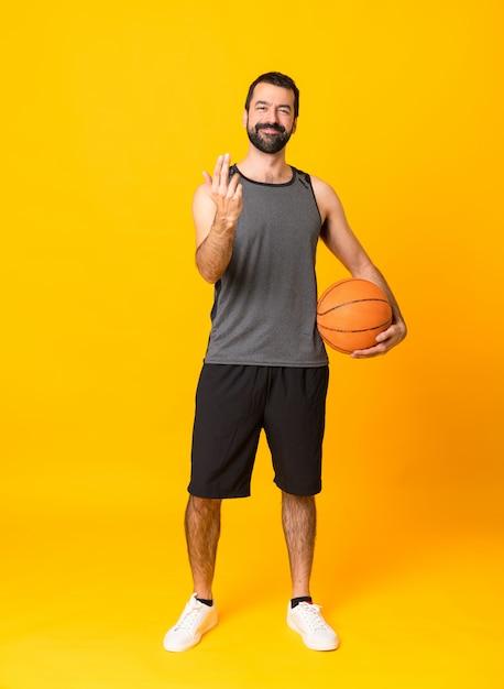 Schuss in voller länge des mannes über dem lokalisierten gelben hintergrund, der basketball spielt und kommende geste tut Premium Fotos