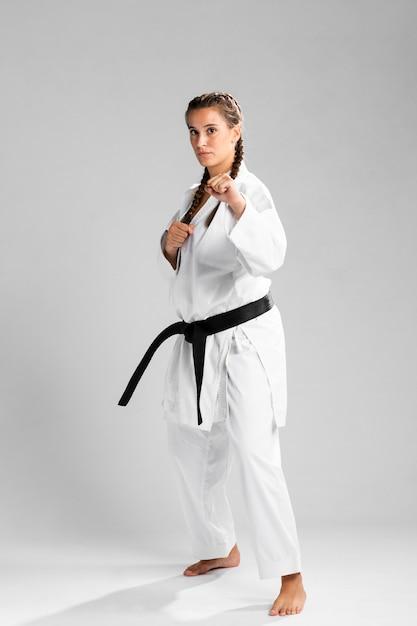 Schuss in voller länge einer frau mit übendem karate des schwarzen gürtels und des kimonos Kostenlose Fotos