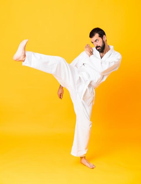 Schuss in voller länge von mandoing karate über lokalisiertem gelb Premium Fotos