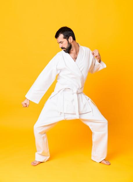 Schuss in voller länge von mandoing karate über lokalisiertem gelbem hintergrund Premium Fotos