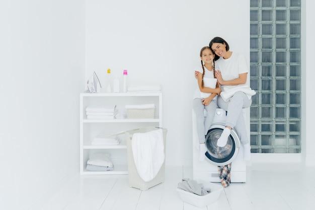 Schuss schöne frau und seine kleine tochter umarmen und lächeln freundlich, sitzen auf waschmaschine, wäschewäsche in waschraum, haben freundliche beziehung, wäsche waschen zu hause. hausarbeit-konzept Premium Fotos