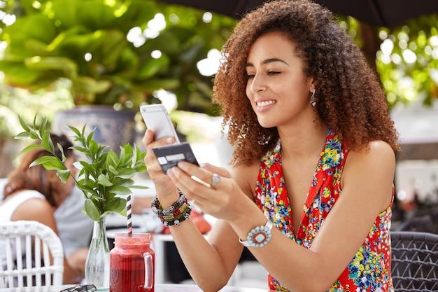Schuss schöne schöne junge frau mit afro-frisur, typennummer der kreditkarte auf dem smartphone, macht online-kauf oder schecks bankkonto Kostenlose Fotos