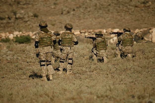 Schuss von armenischen militärsoldaten, die auf einem trockenen feld trainieren Kostenlose Fotos