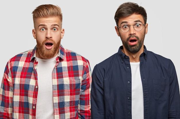 Schuss von attraktiven männlichen begleitern starren mit verängstigten schockierten ausdrücken, kann nicht an eine nicht bestandene prüfung glauben, angst, von der universität ausgeschlossen zu werden, mit angehaltenem atem vor erstaunen schauen Kostenlose Fotos