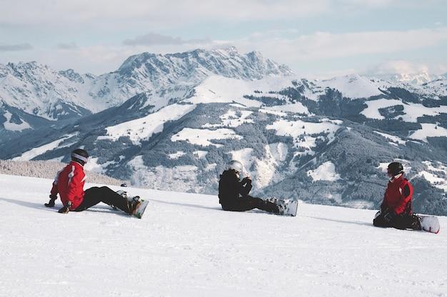 Schuss von snowboardern, die auf schnee sitzen und die weißen berge in tirol, österreich betrachten Kostenlose Fotos